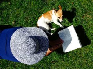 Mujer en gran sombrero para el sol y perro pequeño tumbado en la hierba leyendo un libro
