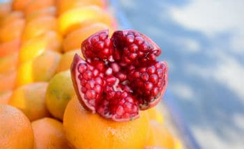 Open pomegranate on pile of fresh oranges on market stall